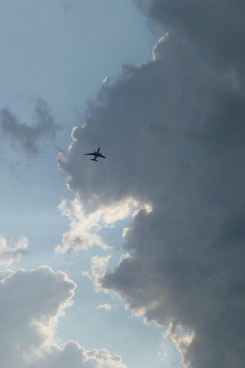 Un avion passe dans un ciel lumineux auquel les sombres nuages donnent du contraste. L'avion, c'est mon père ingénieur, parti pour son dernier vol, sans instruments, sans compas, sans carte...
